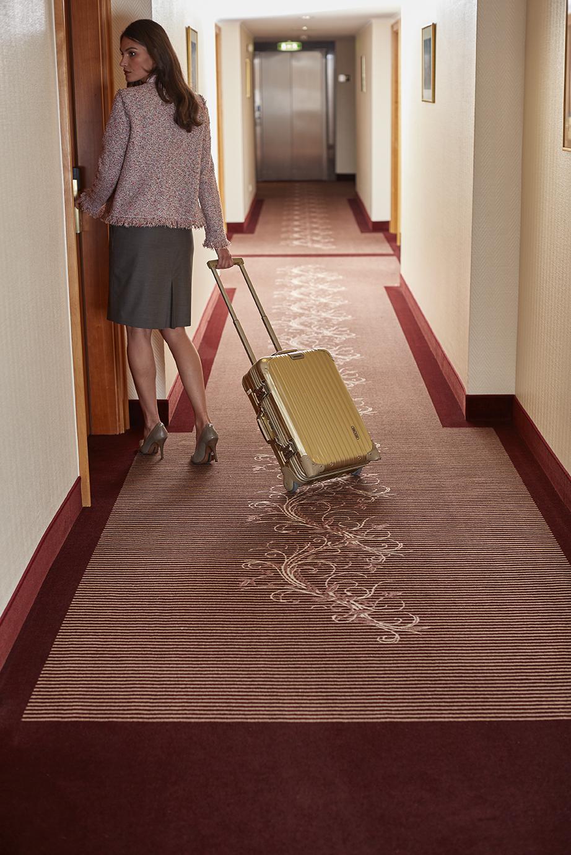 Frau mit Koffer in Hotelfur mit rotem Teppichboden