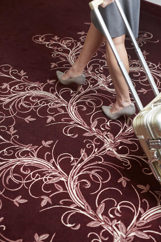 Koffer auf rotem Teppichboden in Hotelflur