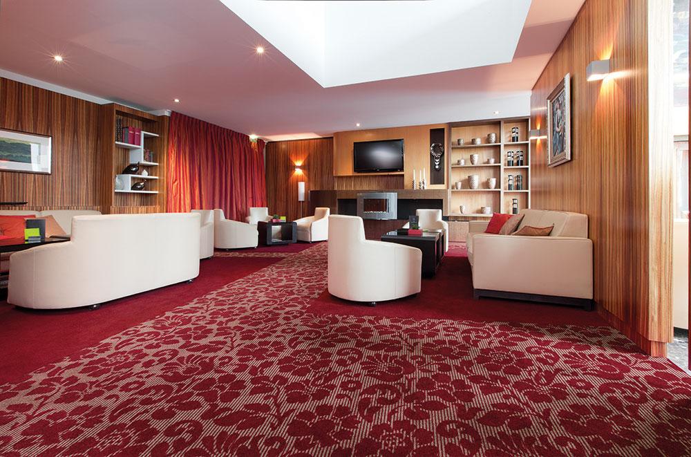Sessel und Sofas in Hotellounge mit rotem Teppichboden