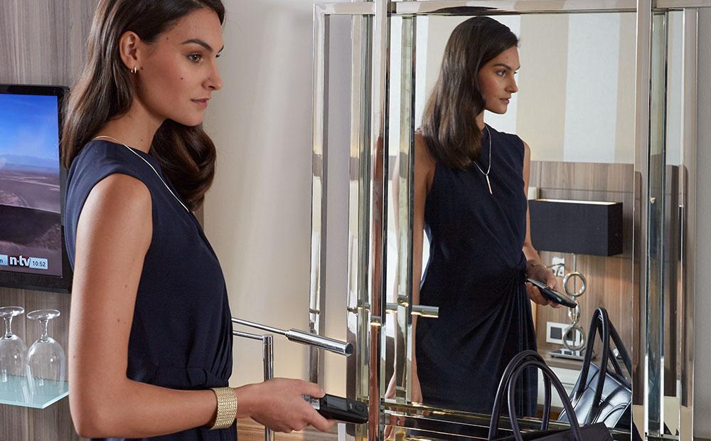 Frau in Hotelzimmer vor Spiegel