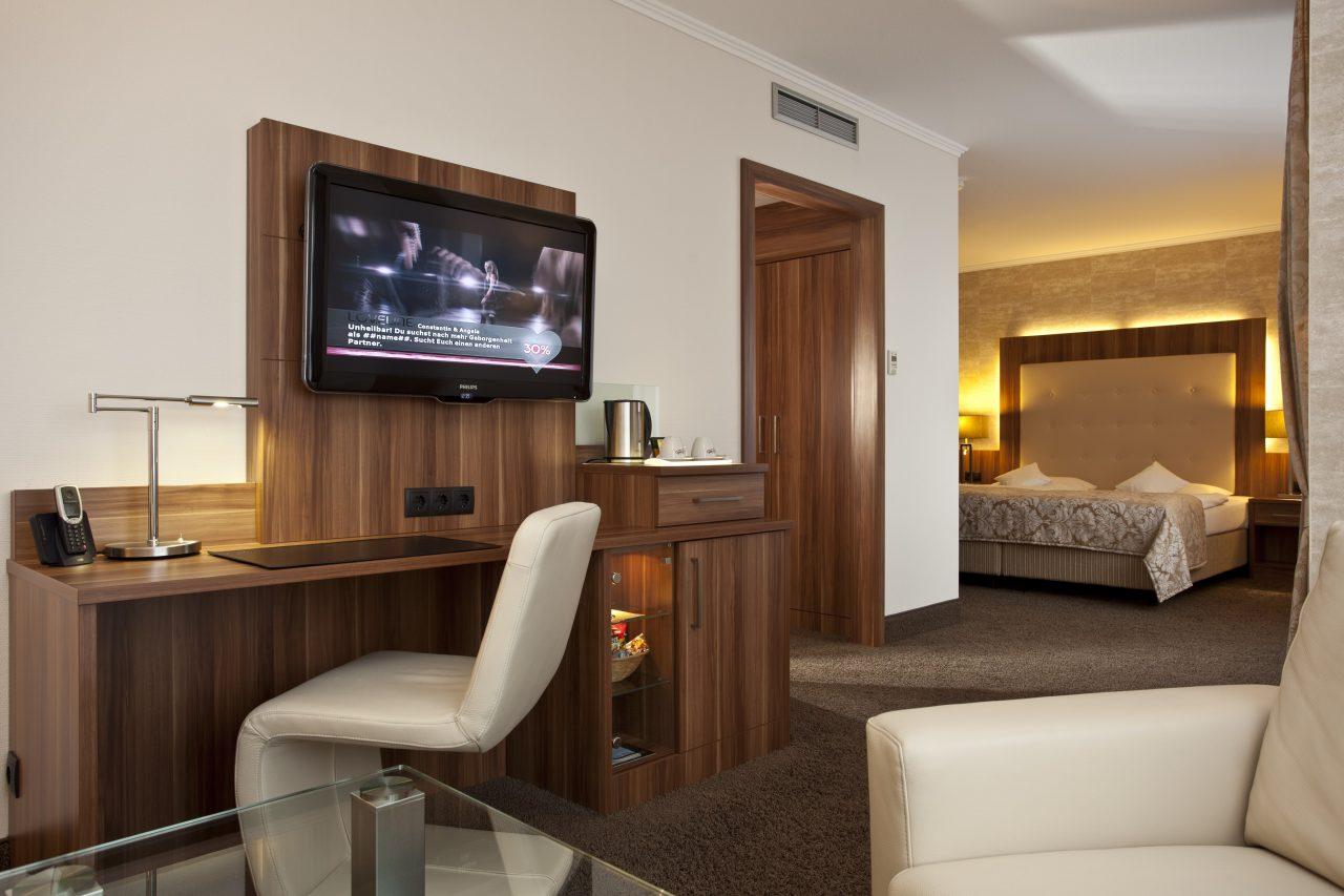 Großes Hotelzimmer mit Schreibtisch im Vordergrund